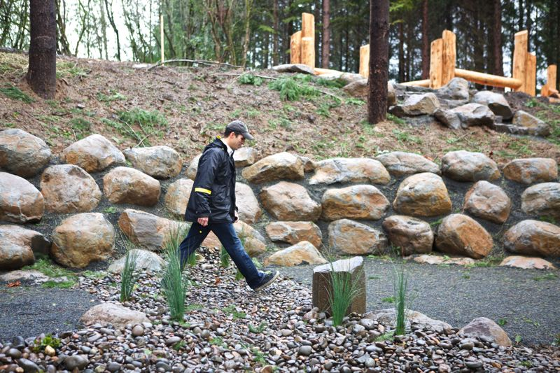 Photo Credit: TIMES PHOTO: JAIME VALDEZ - Tim Bonnin, THPRD lead planner and project manager, walks by a rock wall at Tilbury Park.