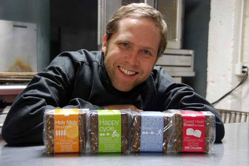 Photo Credit: SUBMITTED PHOTOS - Nick Burger, founder of Regular Portland Bread, poses beside his breads, which are sourdough Scandinavian-style rye breads, dense with nutrients and packed with fiber.