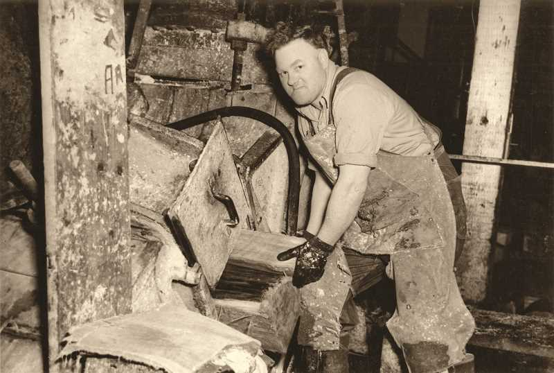 Photo Credit: SUBMITTED PHOTO: WEST LINN PAPER COMPANY - A worker loads the grinder, circa 1950