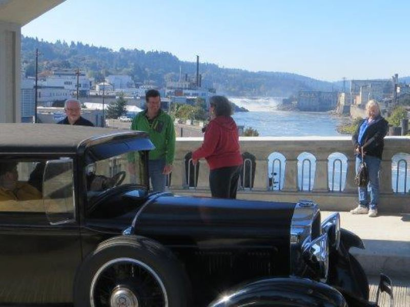 PHOTO COURTESY: WILLAMETTE FALLS HERITAGE AREA COALITION - Willamette Falls is visible is the background as a historic car crosses the Oregon City Arch Bridge, restored to its 1922 grandeur in 2012.