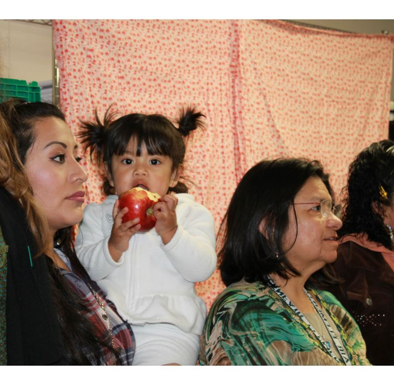 Photo Credit: CONTRIBUTED PHOTO: DARRIN SWAIM - Debanhi Hernandez, center, 2, enjoys an apple at the opening of the Glenfair Elementary community food pantry Feb. 3.