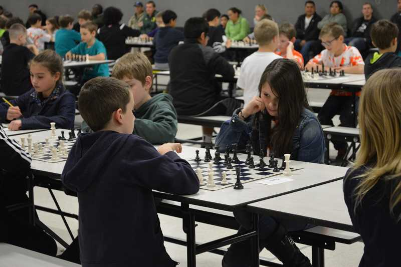Photo Credit: HILLSBORO TRIBUNE PHOTO: KATHY FULLER - Tobias third-grader Emilie Erickson, right, waits for Ian Baldwin, a fourth-grader at Minter Bridge, to make his move at last Saturday's Chess for Success tournament, held at Tobias Elementary School.