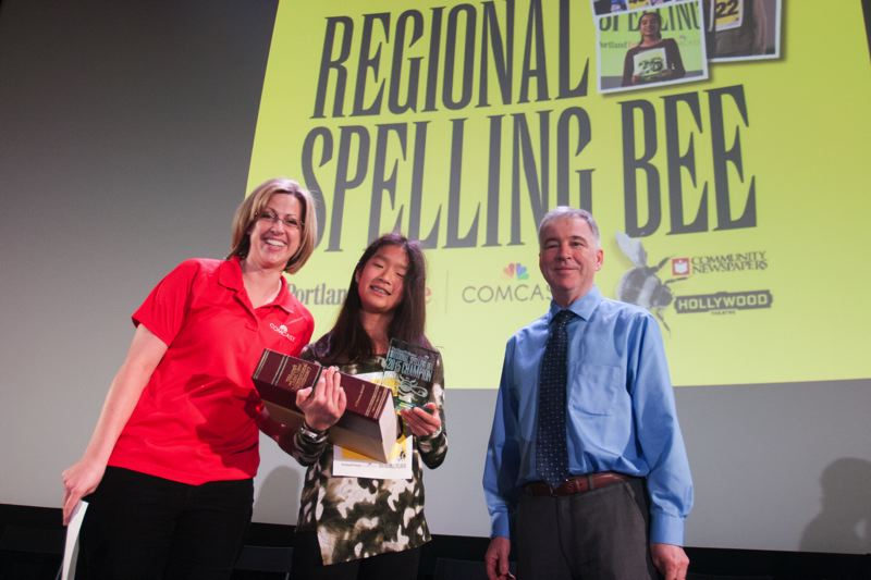 TRIBUNE PHOTO: JIM CLARK - Natalie Cha of Three Rivers Charter School is the winner of the Regional Spelling Bee held at the Hollywood Theater, Saturday, March 7. Cha stands with Rebecca Brown of Comcast, left, and Mark Garber, president of Portland Tribune and Community Newspapers. Cha will compete in the Scripps National Spelling Bee in Washington, D.C., in May.
