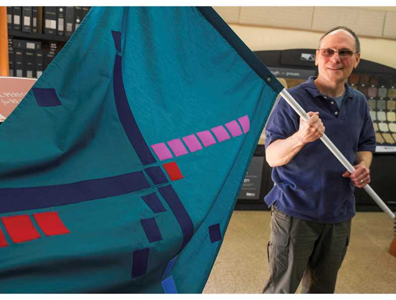 RAY HUGHEY - Nagl Floor Covering co-owner Randy Schultze displays a flag that represents the graphic '80s carpet design at the Portland International Airport. Carpet remnants from the airport will be at Nagl in May and available for purchase.