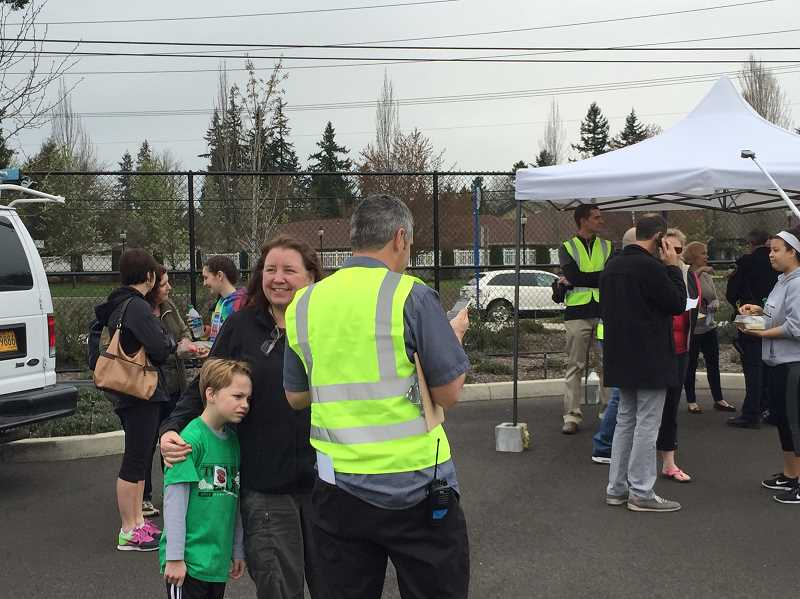 GEOFF PURSINGER - Parents wait to be reunited with their children during an emergency preparedness drill on Friday. The Tigard-Tualatin School District was practicing how it would handle a school evacuation during an emergency, such as a school shooting.