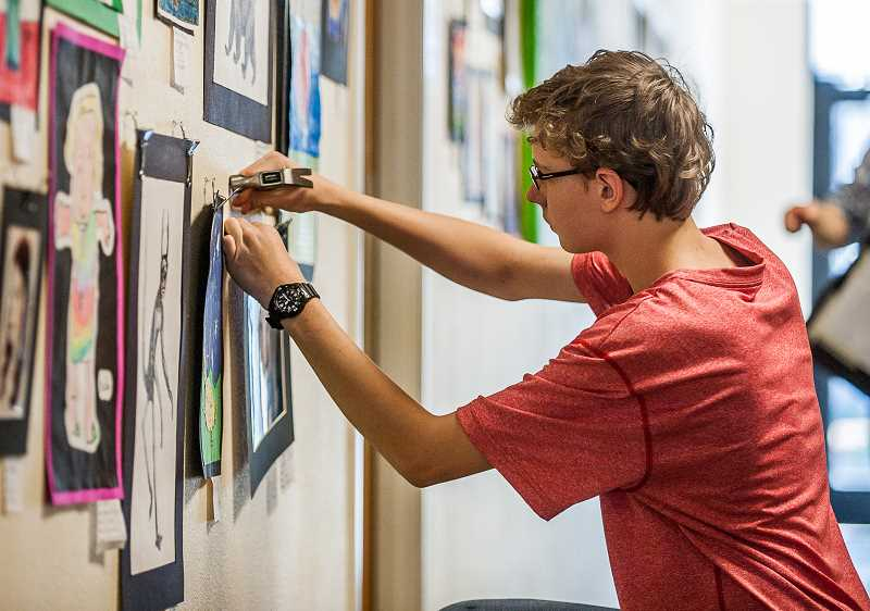 SPOKESMAN FILE PHOTO - Art Tech High School's Isaac Hascall, a freshman at the time, straightens a painting as he helps prepare his school to host last year's district-wide art show. The annual event will be held at ATHS this year on April 18.
