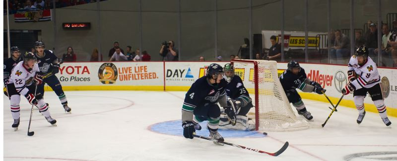 Chase De Leo (right) tries a pass from behind the net for Winterhawks teammate Alex Schoenborn (left).