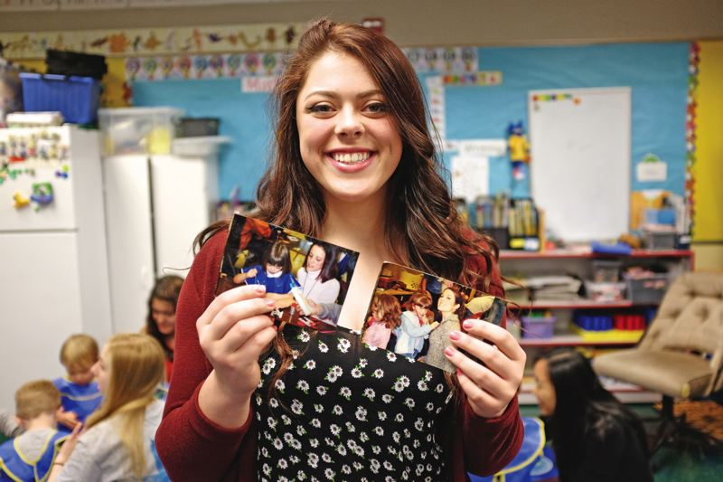 TIMES PHOTO: JAIME VALDEZ - Shannon Tiffany holds pictures of herself when she attended school at the Little Warriors preschool. Tiffany is now a junior at Aloha High School and works with the preschoolers. I used to be like them and played with the same toys, she said.