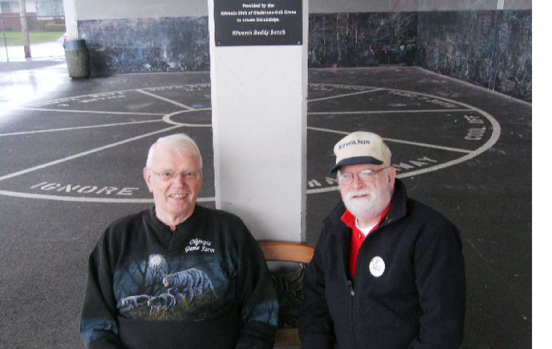 SUBMITTED PHOTO - Kiwanis Club of Gladstone-Oak Grove Secretary Dwayne Snook and President Jerry Deas at Buddy Bench installed at grade school on Kiwanis One Day.