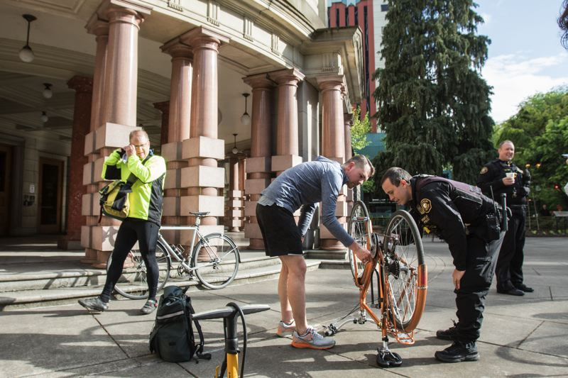 TRIBUNE PHOTO: JONATHAN HOUSE - Christopher Bowker gets help inspecting and registering his bike from Portland Police Officer David Sanders during a City Hall-sponsored breakfast to kick off PDX Bike Month.