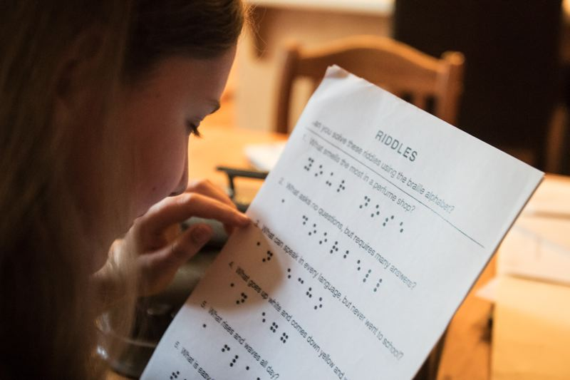 TIMES PHOTO: JONATHAN HOUSE - Clara reads a sheet of riddles that are translated into braille.