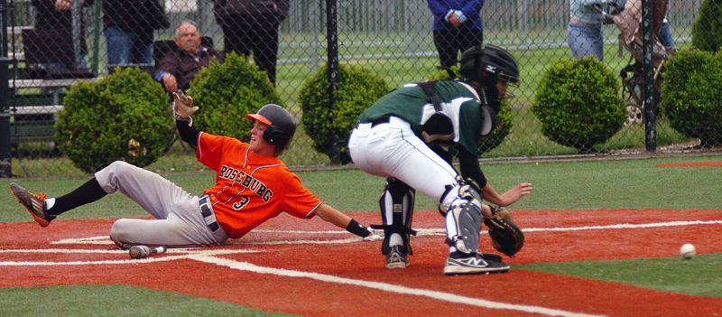 DAN BROOD - Tigard senior catcher Tyler Prock (right) looks to grab the ball as Roseburg's Zack Watkins slides safely home.