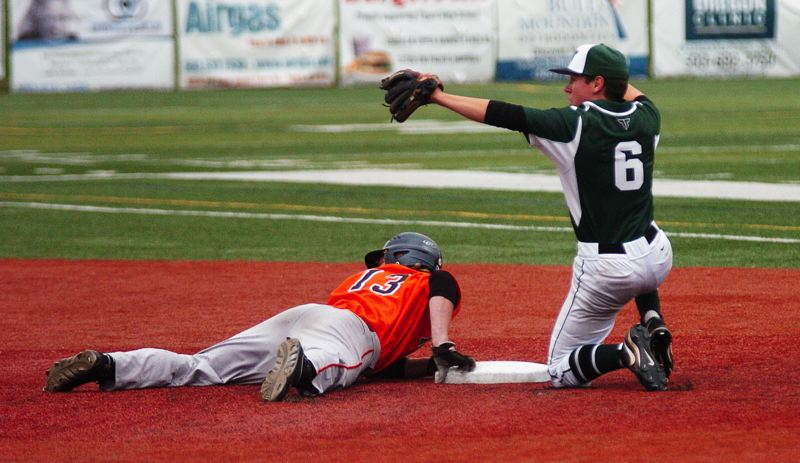 DAN BROOD - Tigard senior second baseman Ben Hildago (right) holds up the ball after tagging out Roseburg senior Isaac Hartwick in the seventh inning of the Tigers' 8-7 state play-in game victory.