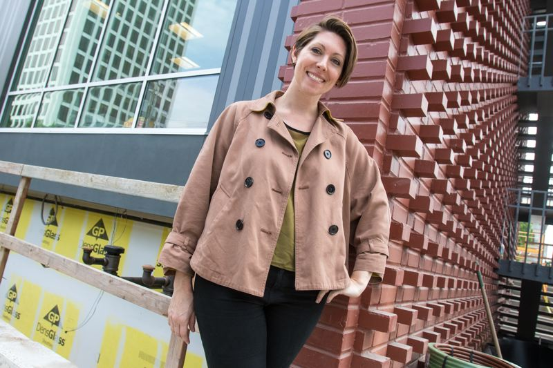 TRIBUNE PHOTO: JONATHAN HOUSE - LEFT: Architect Rachel Brand of Holst Architecture stands in front of some of the original brickwork, one of the few period details saved from the original structure. To appeal to boutiquey types, orange is the accent color and letters are the leitmotif.