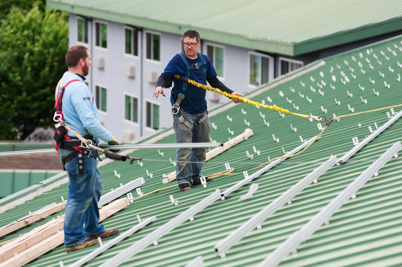 COURTESY NEIL KELLY REMODELING  - Workers install framework to add more than 400 solar panels atop the Best Western in North Portland's Delta Park area.