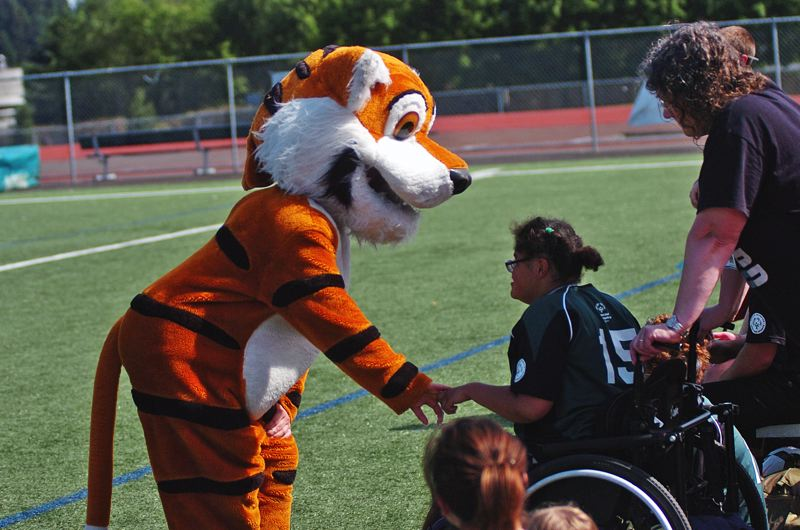 DAN BROOD - The Tigard High School Tiger mascot greets one of the players during the unified soccer match held at the school.