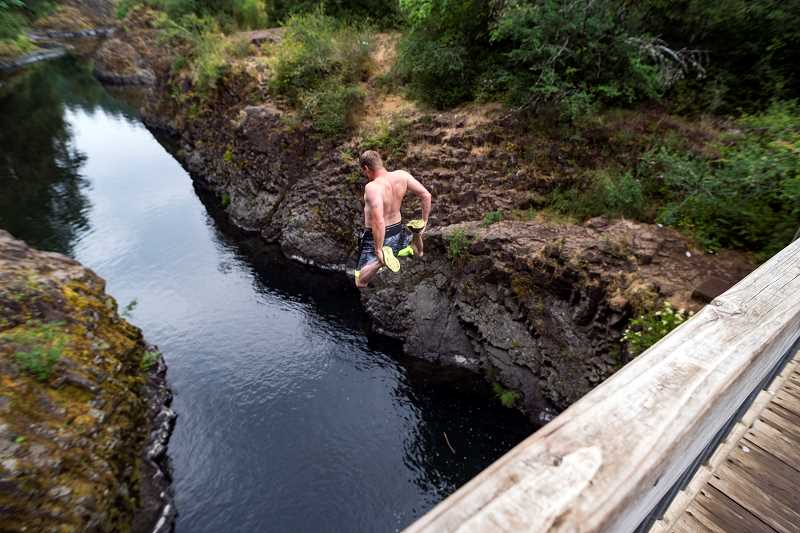 HILLSBORO TRIBUNE PHOTO: CHASE ALLGOOD  - Chad Johnson of Hillsboro jumps into the Wilson River from the Wilson River Footbridge Sunday. Johnson was not only chasing a thrill, he was chasing his nephews lost flip flops.