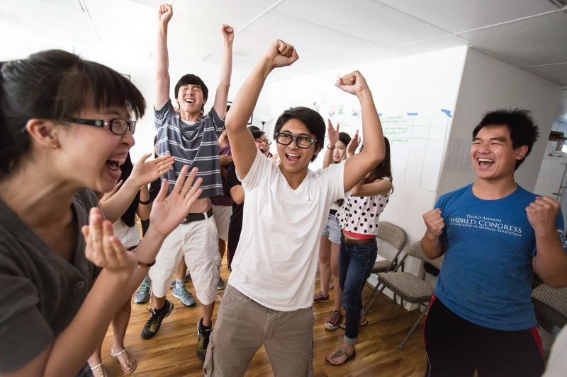 TRIBUNE PHOTO: JONATHAN HOUSE - Ronell Manguino, middle, celebrates a win in a friendly competition during the APANO Ally of Social Justice Bootcamp graduation last week.