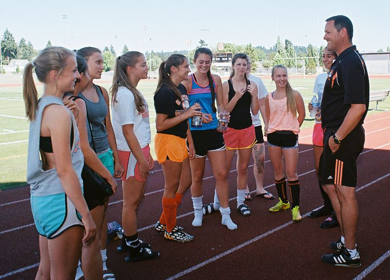 JOHN DENNY - Gladstone coach Greg Hess touches base with some of his soccer players prior to a summer practice.