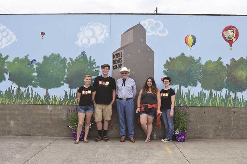 SARA BAILEY - North Marion High School students (from left) Bradi Van Atta, Josh Benson, Hannah Toavs and Alexis Nixon stand with Donald Mayor Daroll Nicholson (center) in front of the new mural at Donald Skate Park, which was unveiled at the festival and was painted by the students.