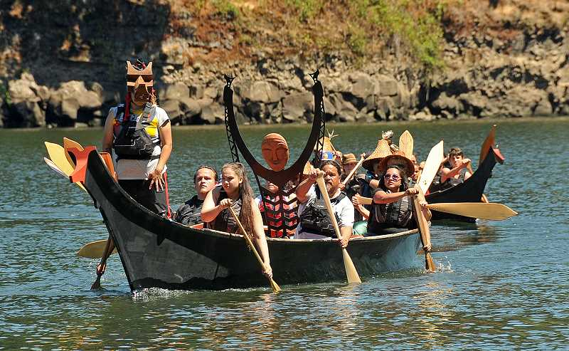 REVIEW PHOTO: VERN UYETAKE - Members of the Confederated Tribes of the Grand Ronde bring a new sculpture to George Rogers Park by canoe Monday afternoon.