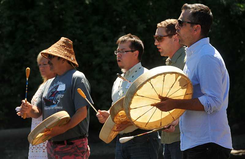 REVIEW PHOTO: VERN UYETAKE - Tribal members Travis Stewart (from right), Jordan Mercier, Dave Harrelson, Joe M and Denise Harvey sing as the sculpture arrives by canoe.