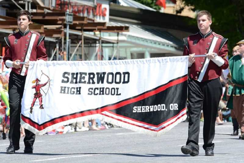 PAMPLIN MEDIA GROUP/DAVID BALL - Sherwood High School students proudly carry a banner identifying the SHS marching band which performed in the Grand Floral Parade during this year's Rose Festival.