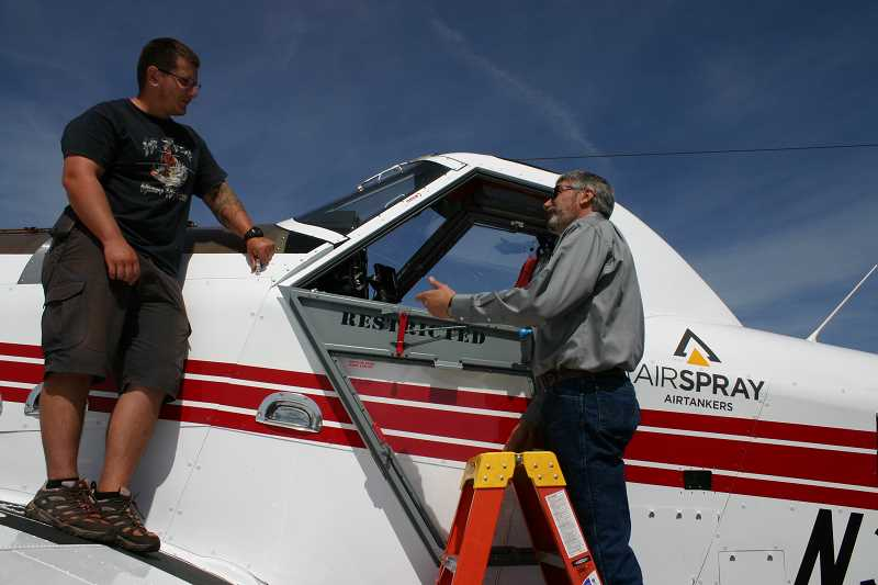 STEVE KADEL - Crook County Commissioner Ken Fahlgren talks with mechanic Sean Dougherty about the air tanker's capabilities.
