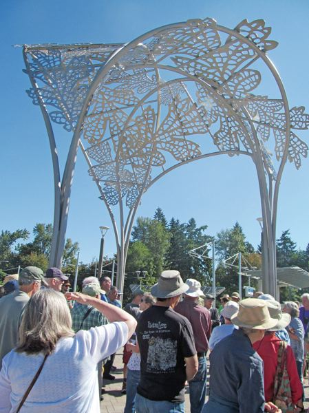 PHOTO BY ELLEN SPITALERI - 'Bower,' Susan Zocala's sculpture, soars over visitors who attended the Trolley Trail art tour on Aug. 7. The piece, festooned with oak leaves, is located at the Southeast Park Street Station in Oak Grove.