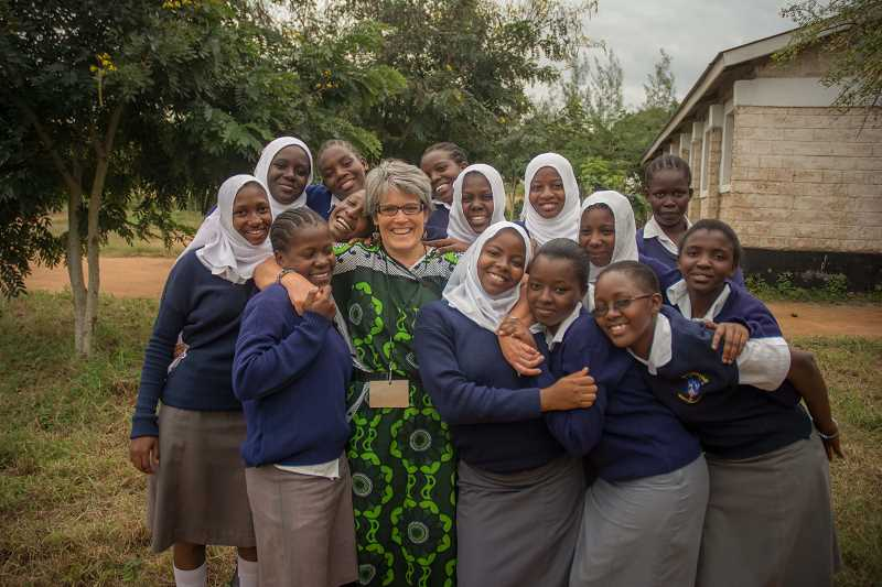 SUBMITTED PHOTOS - Rinda Hayes gets a massive group hug from the school girls from her Kenya Keys program. To say that the kids appreciate what Hayes has done is putting it mildly.