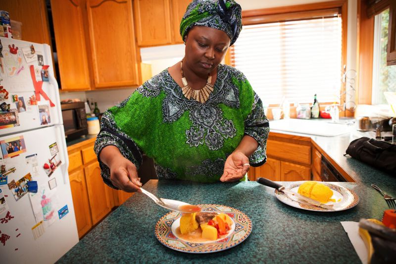 TIMES PHOTO: ADAM WICKHAM - Wambui Machua drizzles gravy over the top of a crockpot meal she served with ugali, a simple boiled cornbread often served in her native Kenya. Machua will serve more time-intensive dishes at her Spices of Africa booth at Saturdays Beaverton Night Market.