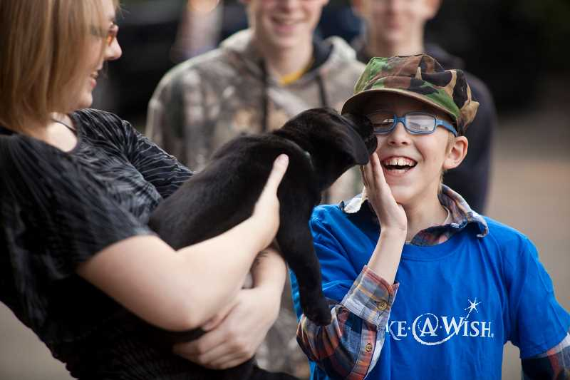 SUBMITTED PHOTO: CAMERON BROWNE  - Marshall Jacobson, 11, gets a kiss from Rocky, who is cradled in the arms of Marshalls sister, Daisha.