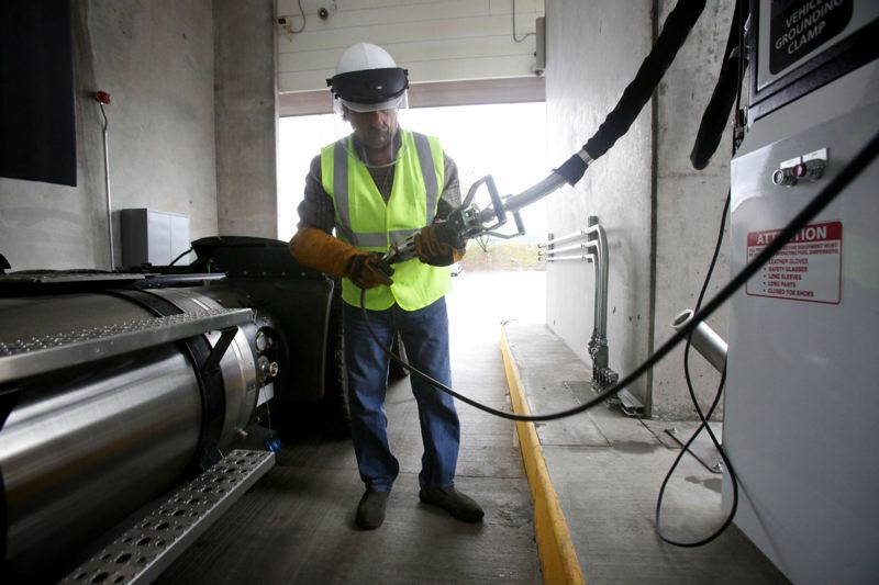 TRIBUNE FILE PHOTO  - Fred Meyer fleet manager Nick Brocato pumps fuel into one of the retailers new LNG-fueled freight trucks in Clackamas. LNG produces fewer pollutants and carbon emissions than diesel fuel.