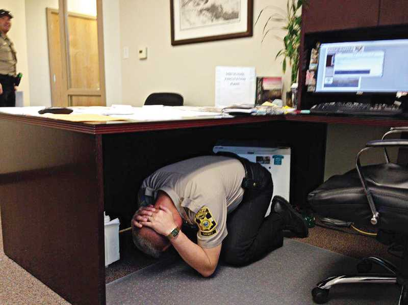 SUBMITTED PHOTO - Sheriff Jim Adkins parctices 'drop, cover, and hold on' during the ShakeOut drill.