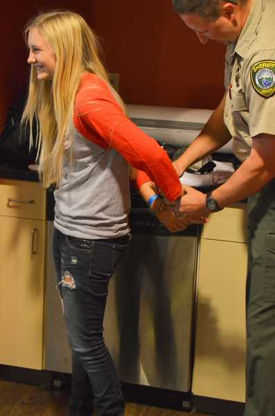 SPOKESMAN PHOTO: JAKE BARTMAN - Wilsonville High School junior Casey Roberts was handcuffed at the Drive with a Cop event by deputy sheriff Bryon O'Neil for failing a mock field sobriety test.