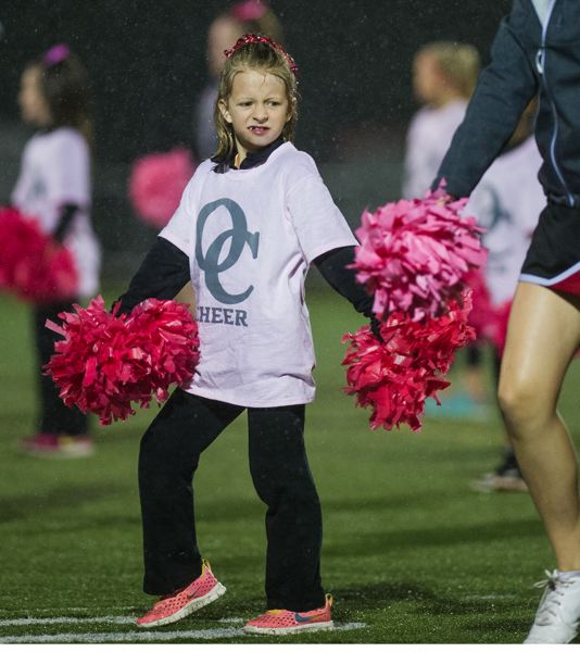 JOHN LARIVIERE - An unidentified junior cheerleader braves the elements to perform at halftime of Friday nights game between Oregon City and Barlow.