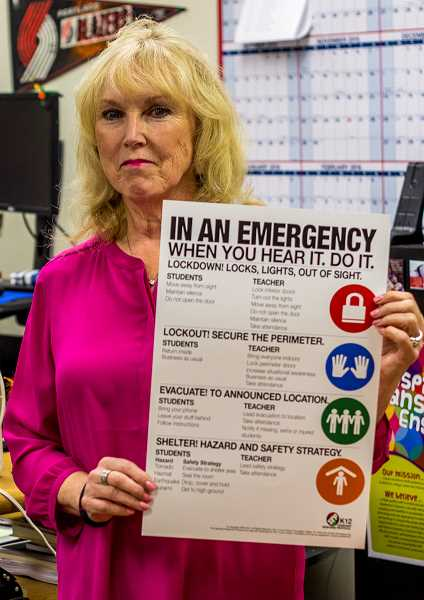 Forest Grove School District Chief of Staff Connie Potter shows off the standard response poster now on display in every classroom and office in the district.