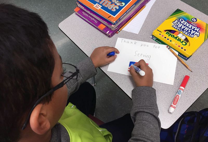 SUBMITTED PHOTO - A student at Pilgrim Lutheran Christian School makes a thank you card for the school's third annual Veterans Day celebration last week.