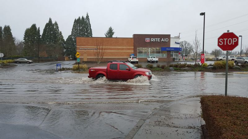 PAMPLIN MEDIA GROUP: JOHN BAKER - A truck leaves a wake in high water at Canby's South Pine Street, just off Highway 99E, Monday afternoon, Dec. 7.