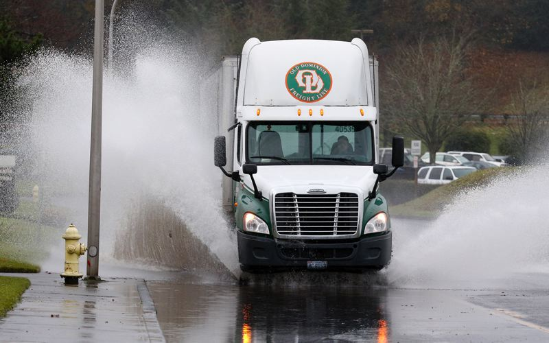 TRIBUNE PHOTO: JONATHAN HOUSE - A truck plows through a flooded street in Milwaukie.