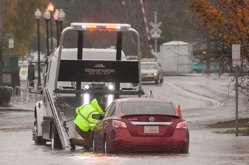 PAMPLIN MEDIA GROUP: JOSH KULLA - A Gresham Towing truck and driver helps free a motorist stranded by high water on Southeast Kelly Avenue Monday morning.