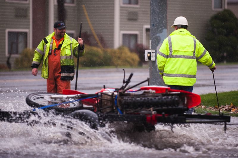 PAMPLIN MEDIA GROUP: JOSH KULLA - Gresham environmental services workers work to unclog a drain at the intersection of Southeast Division Street and Cleveland Avenue Monday, Dec. 7.