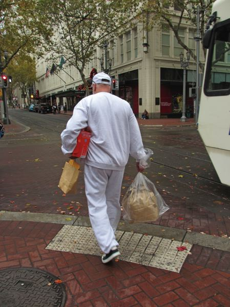 TRIBUNE PHOTO: PETER KORN - Rodney, here walking toward Pioneer Courthouse Square, hates the prison-issue white sweats and plastic bag that mark him as newly released, and a target for drug dealers.