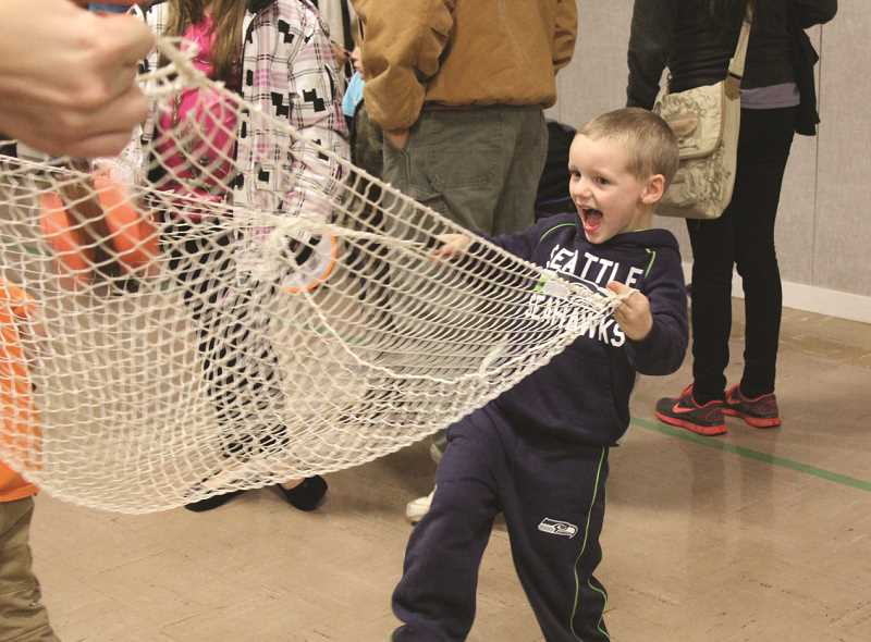 LINDSAY KEEFER - This boy and his mom demonstrate pelele, a game from Spain which uses a net to catch a ball.