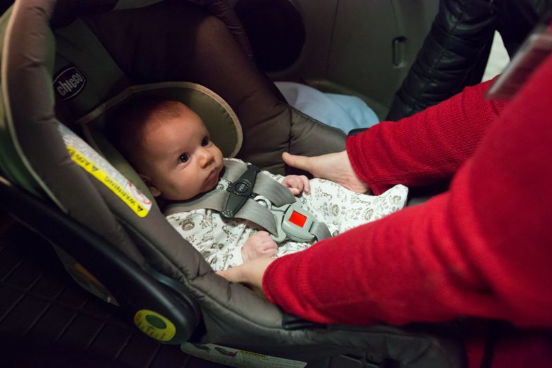 TRIBUNE PHOTO: JONATHAN HOUSE - Wesley Krzeminski gets checked that he's correctly strapped into his car seat at Oregon Health and Science University. New research from OHSU says 91 percent of parents of newborns make serious errors in using or installing car seats.