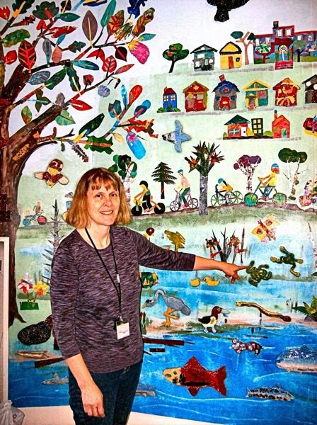 RITA A. LEONARD - Teacher Susan Frisby shows details on one of Llewellyn Elementary Schools two new entry murals.
