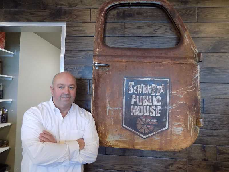GAZETTE PHOTO: RAY PITZ - Schmizza Public House of Sherwood owner Mark Satterwhite, stands in front of the door of a 1939 International pickup (complete with the original patina) with the Schmizza Public House logo painted on it. He found the door in Denver.