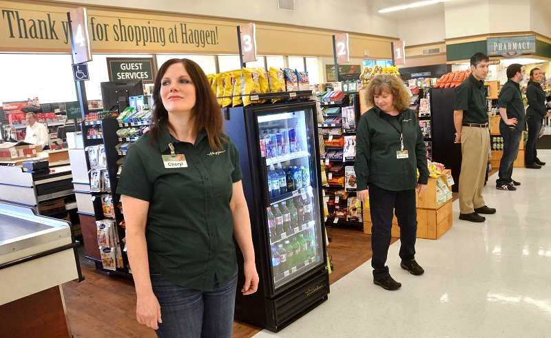 REVIEW PHOTO: VERN UYETAKE - Cashiers await their first customers after the conversion of the Albertsons store on Boones Ferry Road into a Haggen Food & Pharmacy in March.