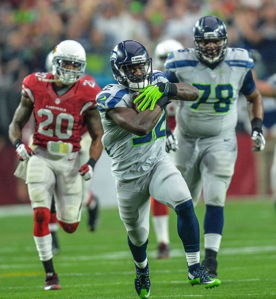 Running back Christine Michael picks up some of his 102 yards on the ground, with Seattle lineman Alvin Bailey bringing up the rear.