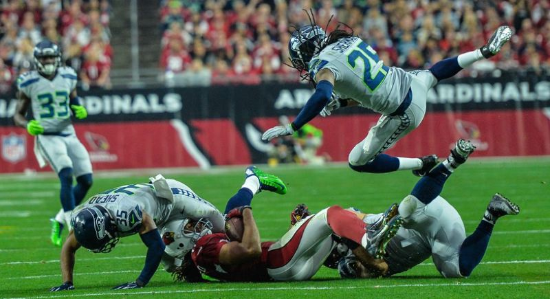 Seattle DBs DeShawn Shead (left) and Richard Sherman help make a play and jar the ball loose from Arizona receiver Larry Fitzgerald.